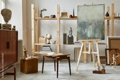 Unique artist workspace interior with stylish teak commode, wooden easel, bookcase, artworks, painting accessories, decoration and elegant personal stuff Fototapet
