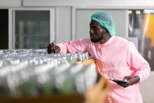 African Male Factory Worker Holding Pen And Clipboard Looking Or Checking For Stocktaking Of Products In Beverage Factory