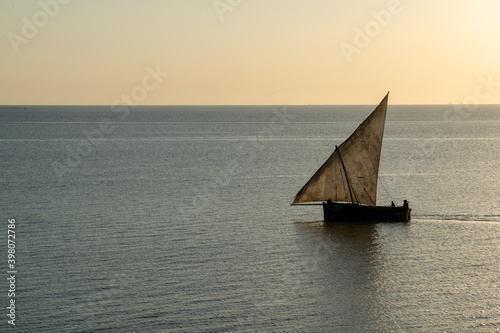 Wooden sailboat on the clear water of Zanzibar island during sunset Wallpaper Mural