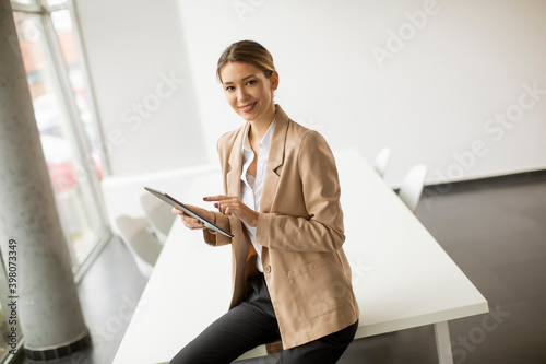 Obraz Happy woman manager holding digital tablet and standing in modern office - fototapety do salonu