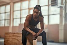 Ethnic Sportswoman Sitting On Box In Gym