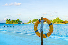 Lifebuoy On Wooden Stand On Tropical Beach On Background Of Blue Water