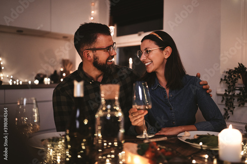 Leinwand Poster Smiling couple talking together during a candlelit dinner party