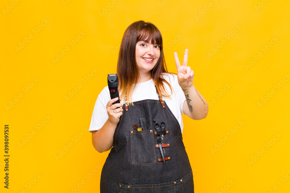 Fototapeta plus size woman smiling and looking happy, carefree and positive, gesturing victory or peace with one hand