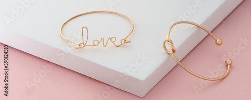 Fotografia, Obraz Word love and knot shape golden bracelets on pink and white background