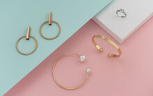 Flat Lay Of Golden Jewelries On Pastel Colors Background