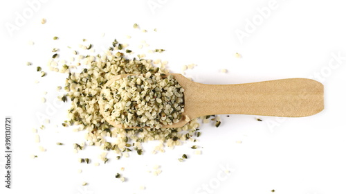 Peeled hemp seed in wooden spoon isolated on white background, top view