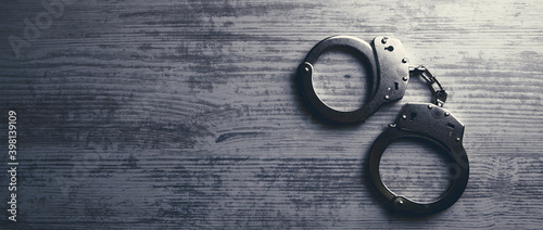 Isolated handcuffs, banner and copy space on a wooden background. Fotobehang