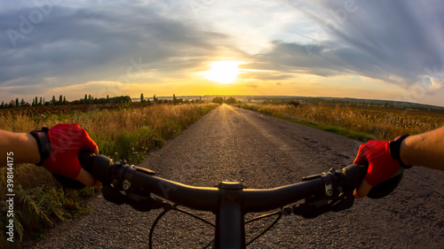 hands on the steering wheel riding a cyclist on the road towards sunset Poster Mural XXL