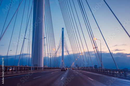 Fototapeta premium Bolshoi Obukhovsky bridge in Saint Petersburg. Automobile Bridge in Russia. White pillars rise above the bridge. Road architecture of Saint Petersburg.