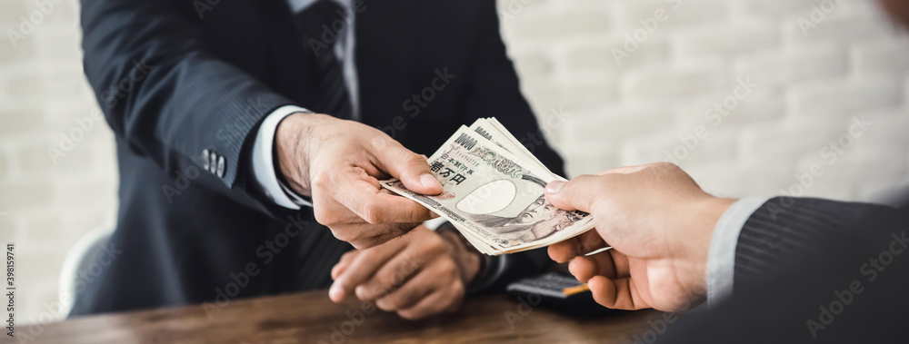 Fototapeta Banner of businessman giving money, Japanese yen currency, to his partner in office  - loan, payment and bribery concept