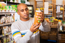 Latin American Man Reading Jar Contents On Label While Shopping In Food Department Of Supermarket