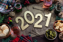 Top Down View Of An Arrangement Of Festive Foods And Decorations With 2021 In The Centre. New Year 2021 Concept