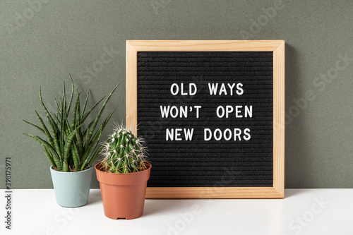 Old Ways Won't Open New Doors. Motivational quote on letter board, cactus, succulent flower on white table. Concept inspirational quote of the day. Front view