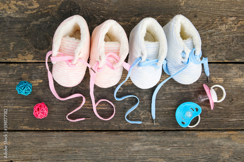 Fototapeta 2021 new year written laces of children's shoes and pacifier on old wooden background. Top view. Flat lay. obraz
