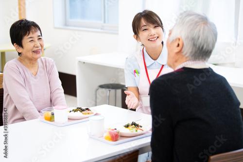 Fotografija 食事中の高齢の入居者たちと介護施設の女性職員