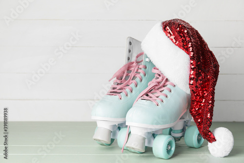 Fototapeta Santa hat with rolling skates on table obraz