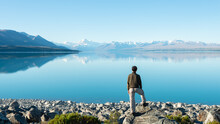 Tourist Standing On The Shore Of Lake Pukaki, Watching Mt Cook Reflected In The Clear Waters