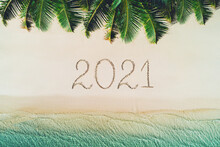 Happy New Year Concept, 2021 Written On The Sand. Summer Holiday On Tropical Island. Palm Trees And Sea Waves.