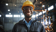Happy Professional Heavy Industry Engineer/Worker Wearing Uniform, Glasses And Hard Hat In A Steel Factory. Smiling African American Industrial Specialist Standing In A Metal Construction Manufacture.