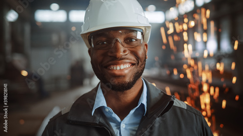 Fotografie, Obraz Happy Professional Heavy Industry Engineer/Worker Wearing Uniform, Glasses and Hard Hat in a Steel Factory