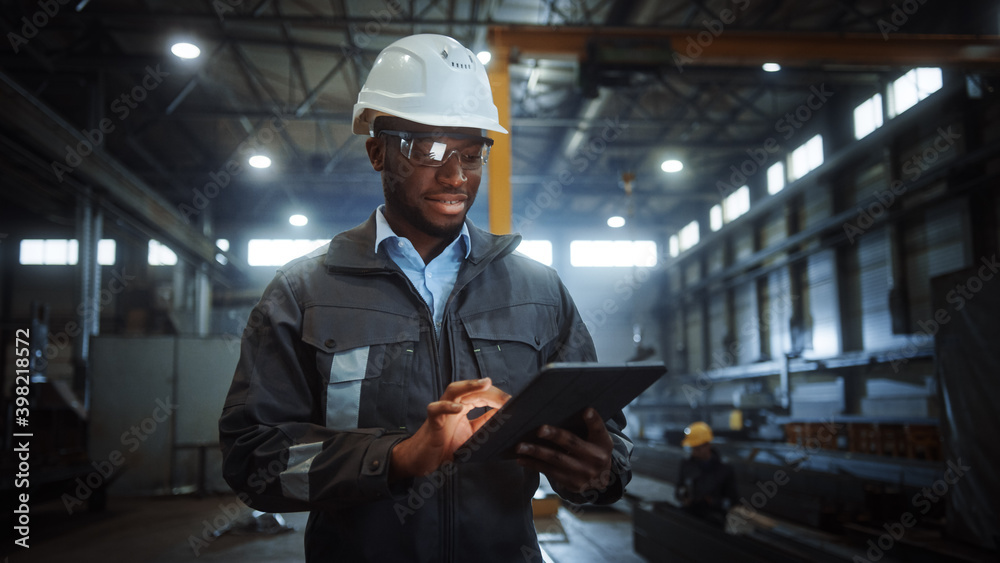 Fototapeta Professional Heavy Industry Engineer Worker Wearing Safety Uniform and Hard Hat Uses Tablet Computer. Smiling African American Industrial Specialist Walking in a Metal Construction Manufacture.
