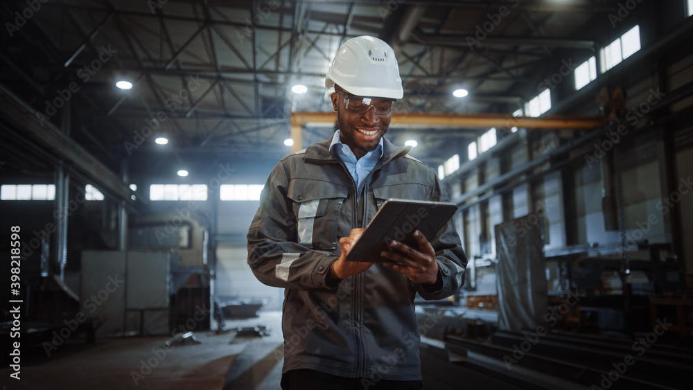Fototapeta Professional Heavy Industry Engineer/Worker Wearing Safety Uniform and Hard Hat Uses Tablet Computer. Smiling African American Industrial Specialist Walking in a Metal Construction Manufacture.