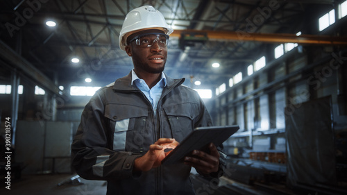 Professional Heavy Industry Engineer/Worker Wearing Safety Uniform and Hard Hat Uses Tablet Computer. Smiling African American Industrial Specialist Walking in a Metal Construction Manufacture. - fototapety na wymiar