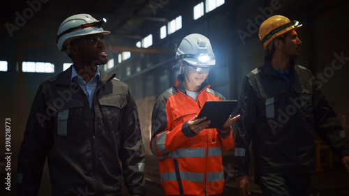 Fotografie, Obraz Three Diverse Multicultural Heavy Industry Engineers and Workers in Uniform Walk in Dark Steel Factory Using Flashlights on Their Hard Hats