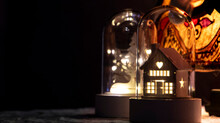 Little Wooden House With Warm Lights Inside A Glass Bell. Christmas Decoration. Dark Background.