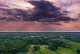 Fototapeta  - Zachmurzone niebo nad leśną równiną. Widok z drona.
