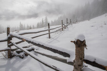 Long Winding Old Wooden Fence On A Snowy Hill In Dense Fog. Selective Focus. Blurred Background.