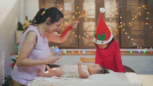 Fotografija Young Asian mother playing with her infant baby girl while happy and enjoy Chris