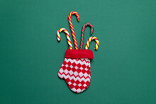 Christmas Candies In A Mitten On A Colored Background. Copy Space. Simple Christmas Card