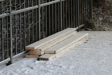 Some Snow-covered Boards Near A Metal Fence
