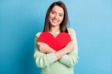 Photo Of Lovely Young Girl Cuddle Red Paper Heart Figure Toothy Smile Wear Green Sweater Isolated Blue Color Background