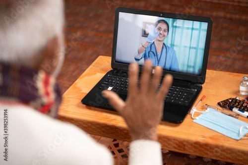 Slika na platnu Shoulder shot of Old man on video with to doctor on laptop screen - concept of O