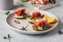 Mini Open Sandwiches With Smoked Salmon, Cream Cheese, Cucumber And Microgreen On Rye Bread, Grey Stone Background. Appetizer With Salmon And Cheese Cream Sauce.