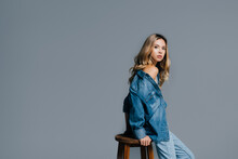 Seductive Woman In Denim Shirt, With Naked Shoulder, Looking At Camera While Leaning On High Stool Isolated On Grey
