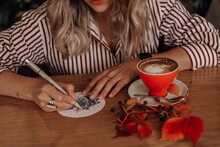 Beautiful Blonde Woman Drinks Coffee And Draws A Mandala On A Piece Of Paper In A Cafe. Zenart, Doodling, Zentangle.