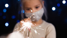 Little Girl Holding Sparkler With Face Mask For New Year And Christmas.