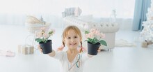A Little Smiling Girl Holds Two Pots Of Pink Flowers In Her Hands. The Child Takes Care Of Home Plants.