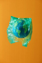 Globe Wrapped In A Plastic Bag. Creative Concept