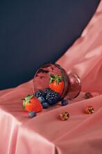 Mix Of Fresh Organic Strawberries, Raspberries, Blueberries And Blackberries In Glass On Table