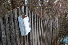 The Old Mailbox On A Wooden Old Fence.