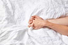 Woman's And Man's Hands Together On Bed.