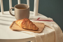 Cup Of Coffee And Croissant On White Chair