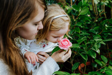 Mother And Daughter Smelling Flower While Walking In Orangery