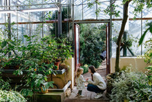 Mother And Daughter Sitting Opposite Each Other In Greenhouse While Hike