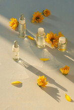 Glass Bottle With Aroma Oil And Chrysanthemum Flowers On Bright Yellow Background. Concept Medicine, Spa. Top View.